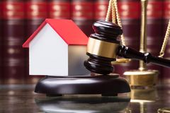 Close-up Of Gavel And House Model. On Sounding Block Royalty Free Stock Photos