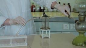 Close-up gedeeltelijke mening van wetenschappers die experiment met reagens en flessen maken sluit omhoog van biotechnologieonder stock footage
