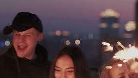 close-up Gelukkige groep vrienden bij betoverende partij met de sterretjes van verlichtingsbengalen in handen, die pret, het glim stock footage