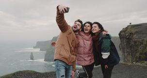 Close-up gelukkige vrienden die beelden in verbazende plaats met mooi landschap met nemen grote Klippen, zij groot glimlachen stock videobeelden