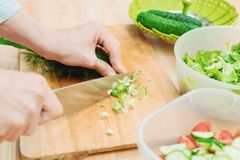 Close-up of gentle female hands slice on the wooden board the stalks of green onions making salad. The concept of a. Vegetarian healthy food and lifestyle Stock Photos