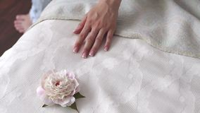 Close-up of a hand of a young girl on the bed, lying next to a peony flower. stock footage