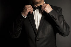 Close-up of  gentleman wearing black tie straightens his bowtie. Stock Photos