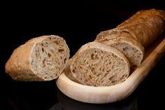 Close-up gesneden baguette op houten plaat en gesneden korst op bl Royalty-vrije Stock Afbeelding