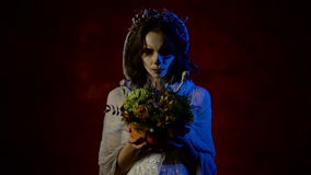 Close up of a ghost of young bride is standing with bunch of flowers in her hands. Mystical woman with art skull make-up stock video footage