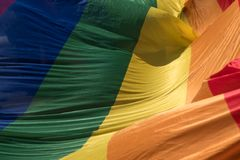Close up of the giant rainbow LGBT flag at the front of the Gay Pride Parade in London 2018. Flag reflects the sunlight. Regent`s Street, London UK. Close up of royalty free stock images