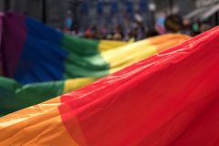 Close up of the giant rainbow LGBT flag at the front of the Gay Pride Parade in London 2018, with people holding the edges.
