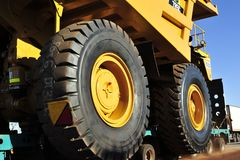 Close up of the Huge Ore Carrier Tyre as it Passes, with the Other Truck Passing on the Left. royalty free stock image