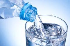 Close-up Gietend glas water van plastic fles op blauwe achtergrond stock afbeeldingen