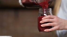 Close-up gietende biet smoothie van mixer aan kruik stock video