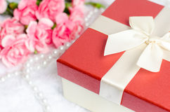 Close up of gift box with pearl necklace and pink carnation Royalty Free Stock Photos