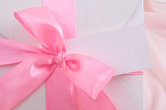 Close up of gift box with pink ribbon and blank card Royalty Free Stock Photography
