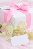 Close up of gift box with pink ribbon, orchid and blank card Stock Image