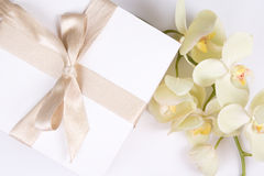 Close up of gift box with ribbon and orchid Royalty Free Stock Photo