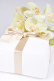 Close up of gift box with ribbon and white orchid Royalty Free Stock Photography