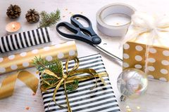 Close up of gift box wrapped in black and white striped and golden dotted paper, pine, cones, christmas toys and wrapping material. S on a white wood old Royalty Free Stock Image