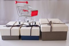 Close-up of gift boxes and shopping cart on white desk stock photo
