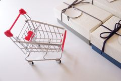 Close-up of gift boxes and shopping cart on white desk stock photos