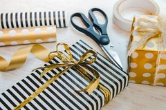 Close up of gift boxes wrapped in black and white striped and golden dotted paper and wrapping materials on a white wood old backg Royalty Free Stock Photos