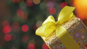 Close up gift a large gift box. Close up gift, a large gift box wrapped in golden paper with a yellow ribbon on a bright festive background stock footage