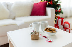 Close up of gift, sweets and cups on table at home stock photo