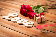 Close up of gift, word love, red roses and hearts Stock Photo