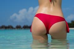 Close up girl back in bikini against ocean beach. Royalty Free Stock Image