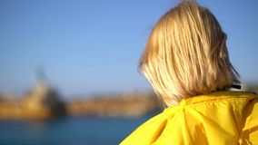Close-up of a girl with blond hair wearing sunglasses and a yellow raincoat standing on a cliff in sunny windy weather.  stock footage