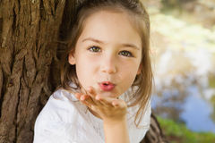 Close-up of a girl blowing a kiss at park Stock Image