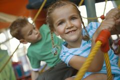 Close-up of a girl with a boy on a rope climbing net Stock Images