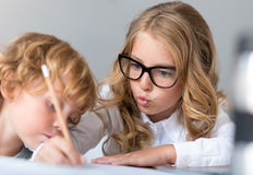 Close up of girl and boy writing. Look attentively. Sophisticated little girl with glasses writing and explaining it to the little boy who looking attentively at Royalty Free Stock Photo