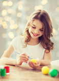 Close up of girl with brush coloring easter eggs. Easter, holiday and child concept - close up of girl with brush coloring easter eggs over lights background royalty free stock photography