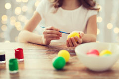Close up of girl with brush coloring easter eggs. Easter, holiday and child concept - close up of girl with brush coloring easter eggs over lights background stock photography