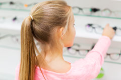 Close up of girl choosing glasses at optics store. Health care, people, eyesight and vision concept - close up of little girl choosing glasses at optics store Royalty Free Stock Photography