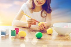 Close up of girl coloring easter eggs. Easter, holiday tradition and child concept - close up of girl coloring eggs over sky background Royalty Free Stock Photos