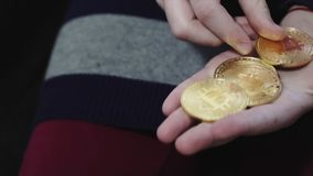 Close-up girl counts golden bitcoin. Financial stock video footage