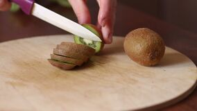 Close-up girl cuts kiwi on a wooden Board. Close-up of woman`s hands slicing kiwi on wooden Board. Hand slicing a kiwi with a knife on wooden board, close-up stock footage