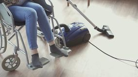 Close up girl with disabilities in a wheelchair vacuuming. Close up disabled girl in a wheelchair is cleaning vacuuming at home stock video footage