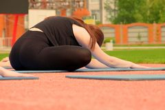 Close-up Girl doing exercise butterfly and stretches her back. Exercises for the splits. Fitness classes in the fresh air. Close-up. Girl doing exercise royalty free stock image