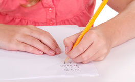 Close-up of a girl doing math problems. On white paper Royalty Free Stock Image