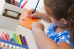 Close-up of a girl drawing on orange paper Stock Photography