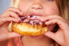 Close Up Of Girl Eating Iced Donut Stock Photography