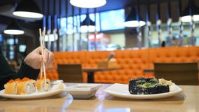 Close-up of girl eating sushi rolls in japan restaurant royalty free stock images