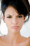 Close up on girl frowning, looking unhappy and stressed. Stock Photos
