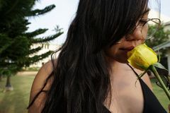 Close-up of girl with glasses, holding yellow rose flower. royalty free stock image