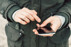 Close-up of a girl in a green jacket using a mobile phone with a Stock Photography