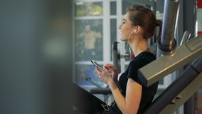Close-up of a girl in the gym with a phone and a headset stock footage