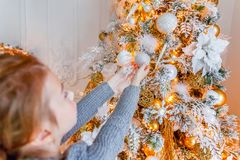 Close up girl hands decorating Christmas tree at home stock image