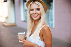 Close up of girl in hat holding take away cup Royalty Free Stock Photos