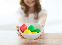 Close up of girl holding bowl with colored eggs Royalty Free Stock Photography